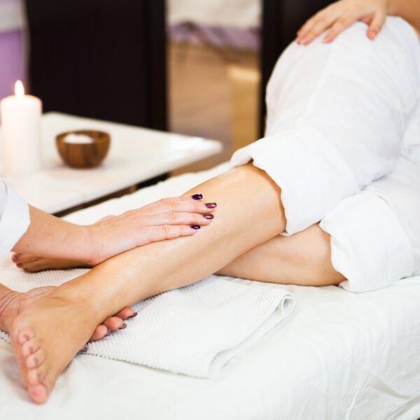 Young pregnant woman take relaxing foot massage at beauty spa salon. Close-up.  Spa treatment. Сoncept of beauty and health