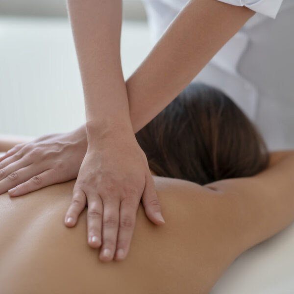 Upper back massage. Young woman lying down and having back massage