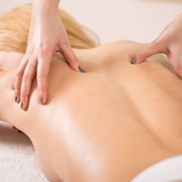 Therapist pressing tight muscles on woman's back